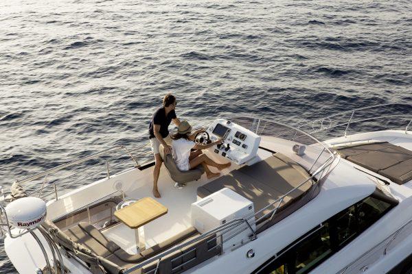 Prestige 420 von Prestige Boats. Die Flybridge aus der Vogelperspektive - Eine Frau Sonnenhut sitzt am Steuer ein Mann steht daneben schaut in die Ferne